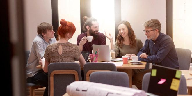 Fem mennesker som sitter og snakker med hverandre rundt et møtebord.