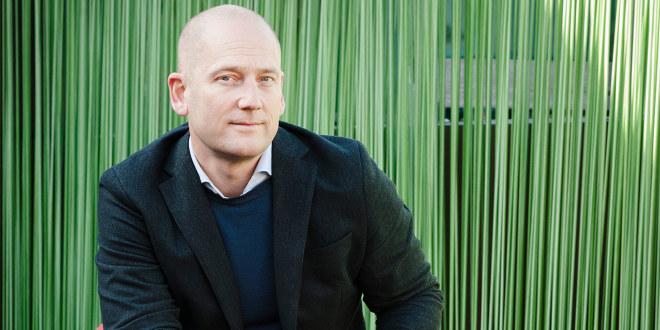 Portrett av Steffen Handal med grønn bakgrunn