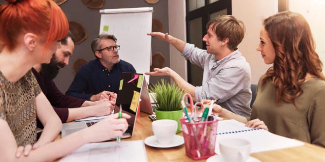 Rundt et møtebord sitter det fem personer. En av møtedeltakerne viser noe med hendene som de andre følger med på.