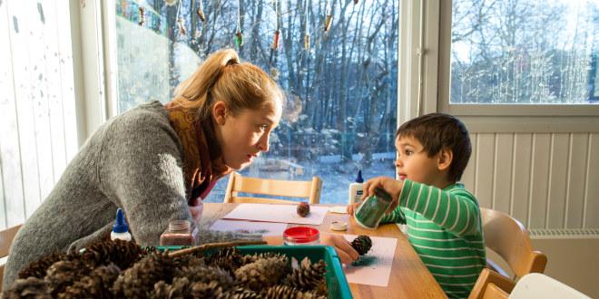 En barnehagelærer sitter ved et bord sammen med et barn og sammen lager de julepynt ut av kongler.