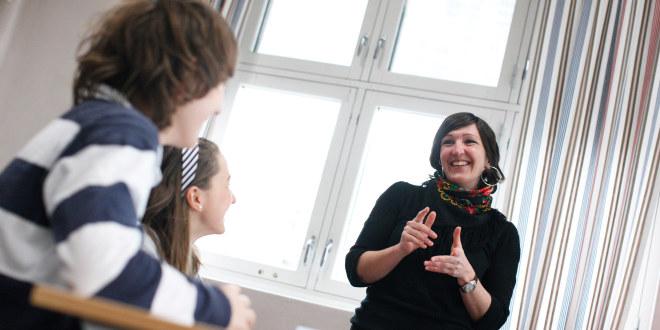 Lærer snakker og smiler til to elever i et klasserom