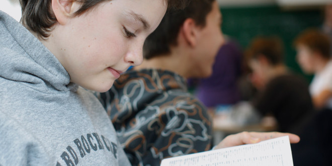 Vi er i et klasserom. Nærbilde av en gutt som leser i en bok.