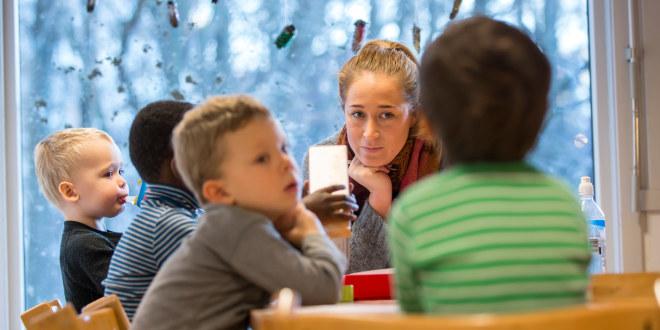 Fire barn rundt et bord sammen med en voksen dame. I en barnehage.