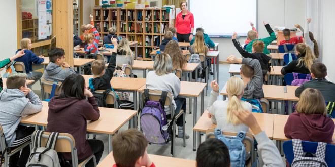 Klasserom med mange elever som rekker opp hånda. Lærer står og ser ut over klassen.