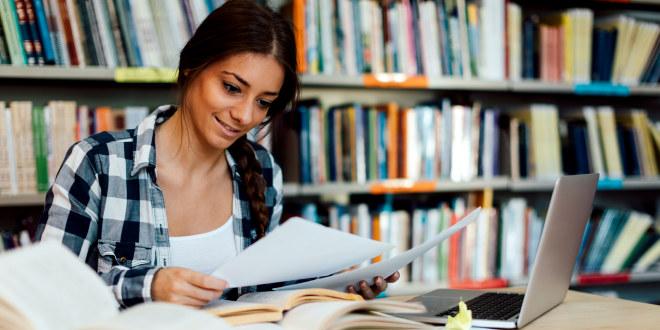 Student som leser papirer i et bibliotek.