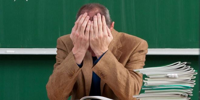 Mannlig lærer sitter på kateteret med hendene foran ansiktet og er fortvilet.
