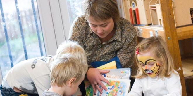Barnehagelærer sitter med bøker og tre barn i en barnehage.