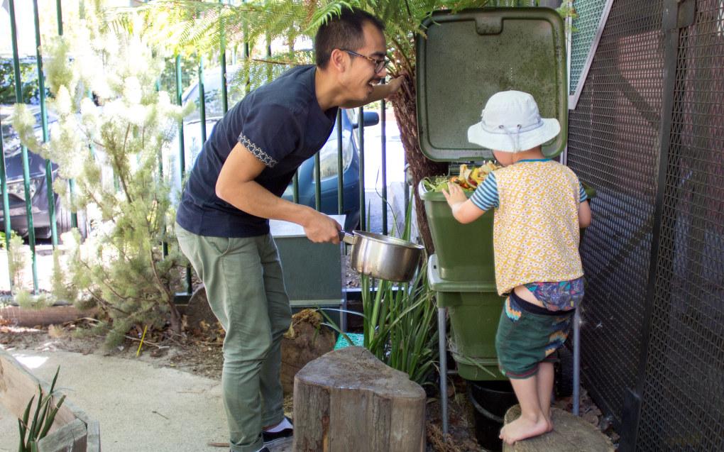 Den australske barnehagelæreren Tommy Tan hjelper en av de minste i barnehagen med å mate marken i markfarmen med matavfall fra barnehagens kjøkken. Foto: Andrea Thiis- Evensen
