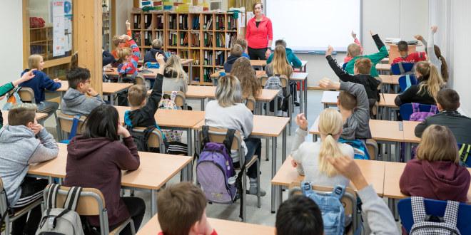 Klasserom med mange elever som rekker opp hånda. En lærer står ved tavla og ser utover klassen