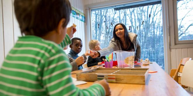 Barnehagebarn arbeider med kunst og håndverk med en barnehagelærer
