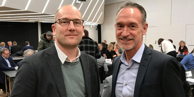Steffen Handal, forhandlingsleder i Unio KS og områdedirektør Arbeidsliv Tor Arne Gangsø i KS samme foran mennesker i en sal.