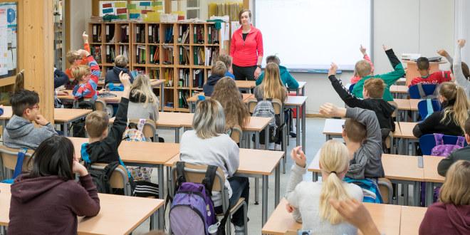 Kvinnelig lærer står foran klassen der flere elever rekker opp hånden.