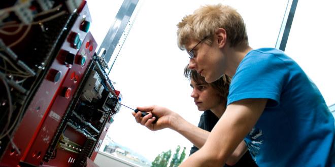 To elever i videregående skole jobber med verktøy på en maskin
