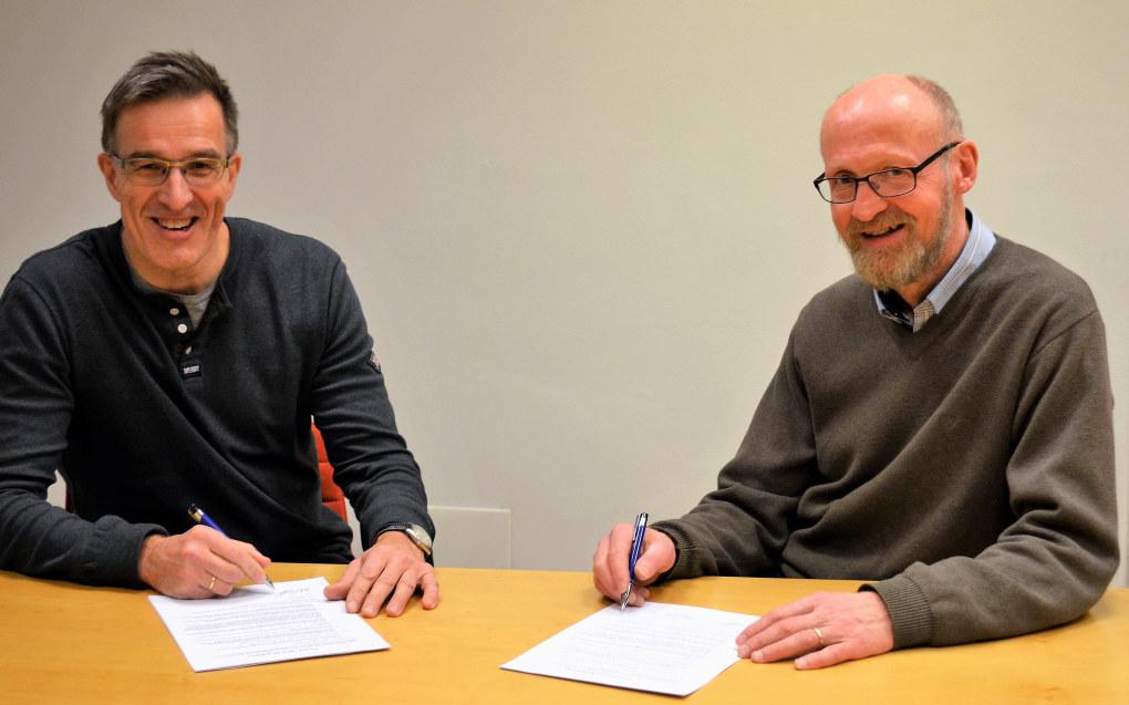 Karsten K. Langfeldt fra KS (t.v.) og Yngve Slettholm fra Kopinor signerer protokollen etter at den nye avtalen for kommunesektoren er klar. Foto Hege Lunde