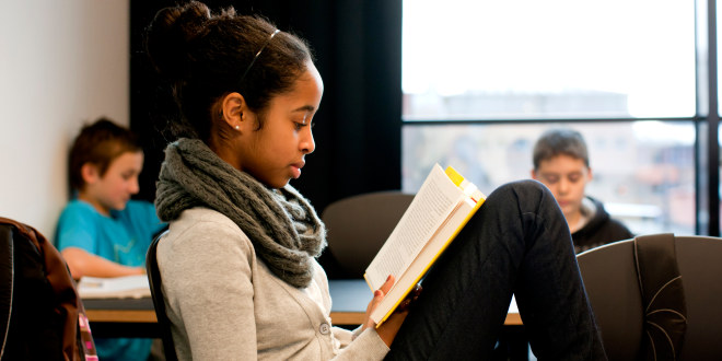 Jente leser bok i klasserom.