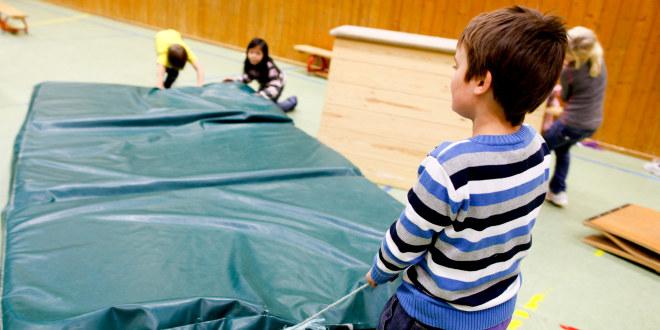 Unge elever setter opp diverse utstyr for fysiske aktiviteter i en gymsal