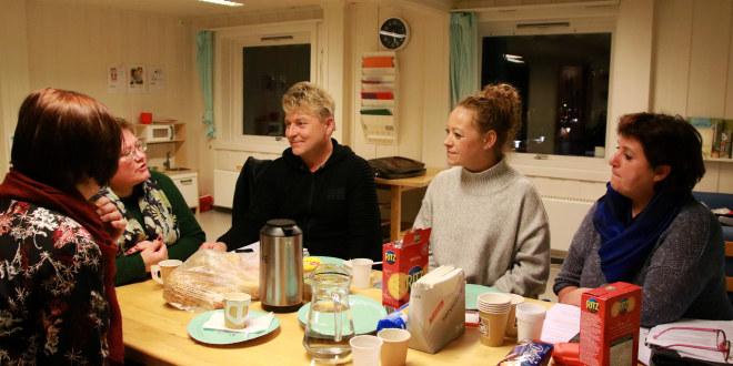 Fire damer og en mann sitter rundt et bord i en barnehage.