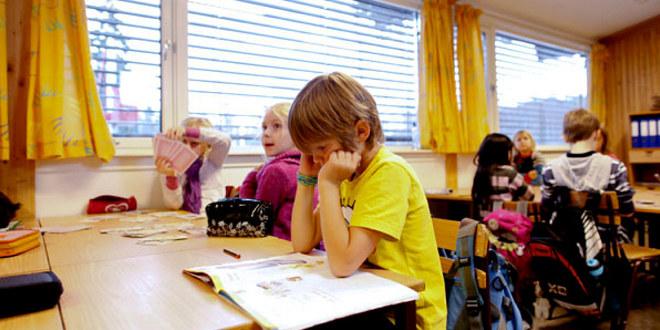 Vi ser barnskoleelver ved pultene sine. En leser, en ser på tavla, en sitter med kort. Noen ser vi ryggen på.