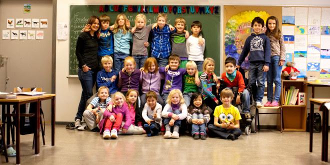 Vi ser en skoleklasse fotografert som et tradisjonelt klassebilde, med alle elevene pluss læreren samlet foran tavla. Alle ser på fotografen og ser fornøyde ut!