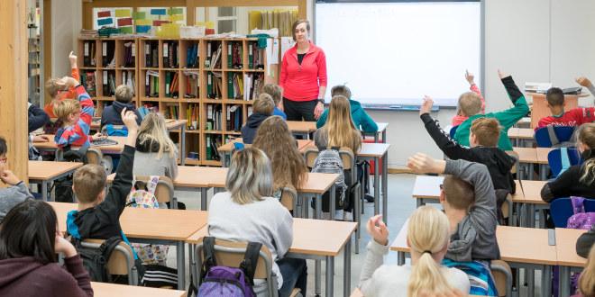 Kvinnelig lærer foran elever i et klasserom.