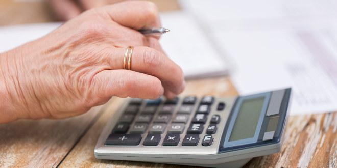 Vi ser en hånd som regner på en liten kalkulator.