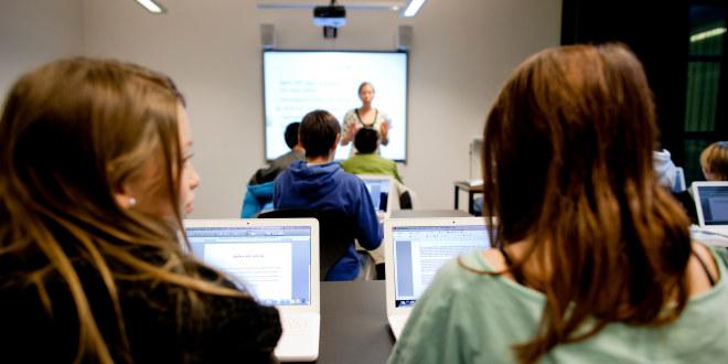 Elever sitter klasserom med pc foran seg samtidig som lærer står foran elektronisk tavle og underviser.