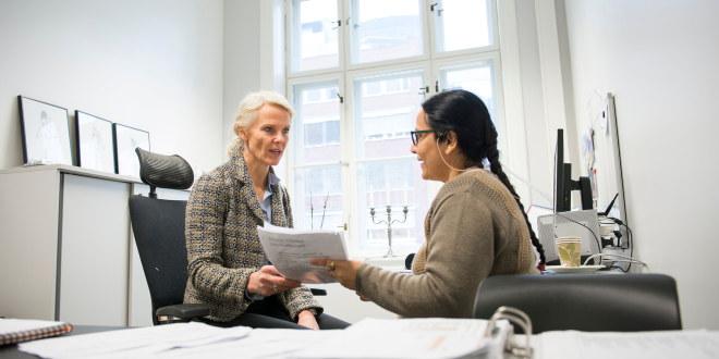 To damer snakker sammen på et kontor. Den ene har lyst hår, den andre mørkt.