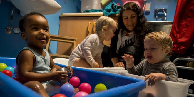 Tre barnehagebarn leker med baller i bøtter med vann. Kvinnelig barnehagelærer hjelper til.