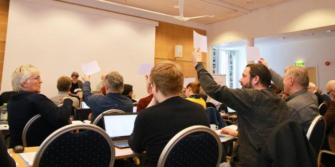 Mennesker sitter i konferanserom, viser delegatnr for å få ordet.