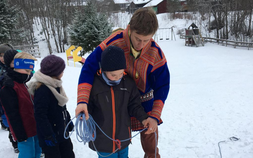 Her prøver elevene seg på lassokasting. Ikke en helt lett øvelse. Ole Vars Danielsen instruerer Henri Eiler. Elvene fikk prøve å treffe reinhorn. For å øke vanskelighetsgraden tok en lærer hornene på hodet og sprang rundt. Foto: Privat