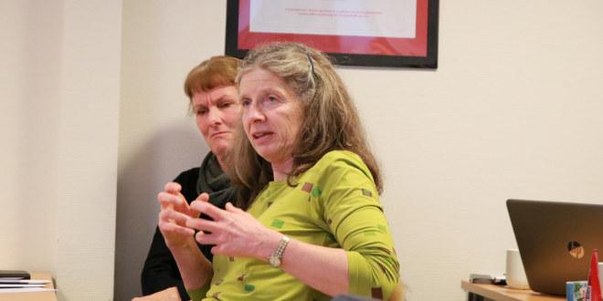 En dame med grønn genser og langt, grålig hår gestikulerer med armene og snakker. En annen dame sitter ved siden av henne.