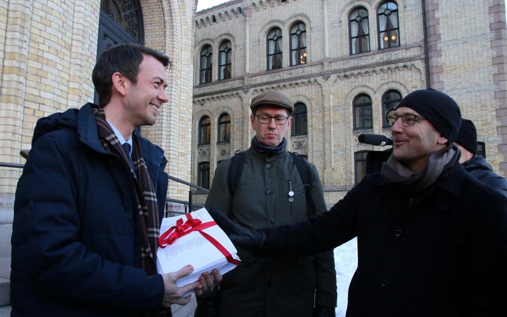 Det var en tung bunke med papir med protestunderskrifter Høyres Kent Gudmundsen (t.v.) fikk av Steffen Handal utenfor Stortinget. I bakgrunnen står Hans Ole Rian fra Musikernes fellesorganisasjon. Foto: Jørgen Jelstad.