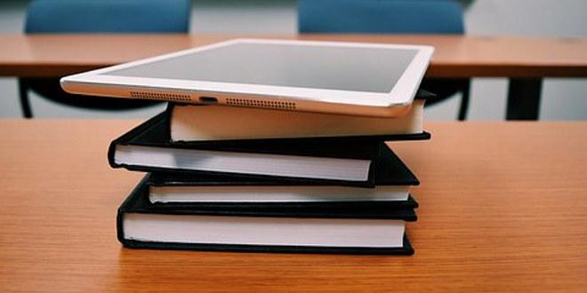 Nettbrett på stabel av bøker på et bord