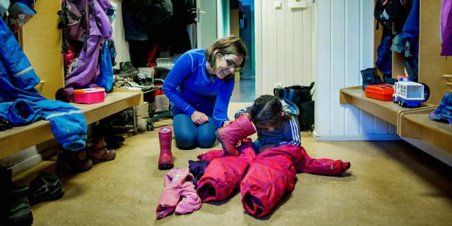 Barnehagelærer hjelper barn med å kle på seg.