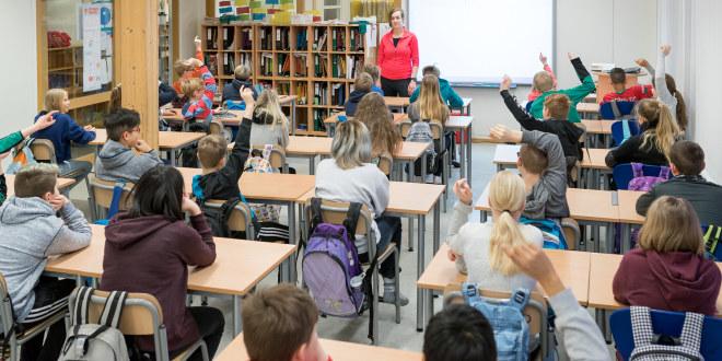 Stor klasse på barneskolen. Lærer står ved kateteret og mange elever har hendene i været.