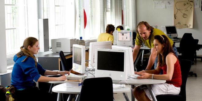 To elever sitter foran pc. Mannlig lærer hjelper en av elevene.