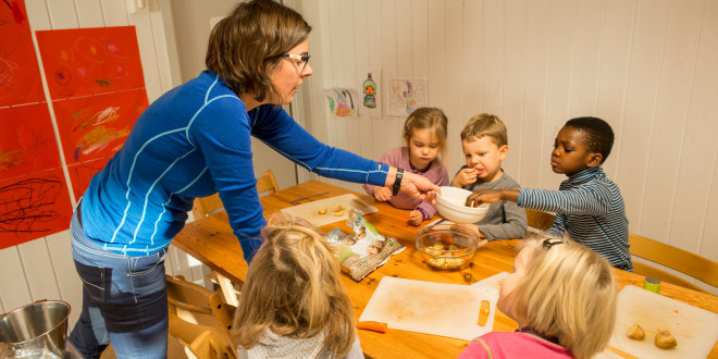 Barnehagelærer deler ut poteter til barn rundt et bord