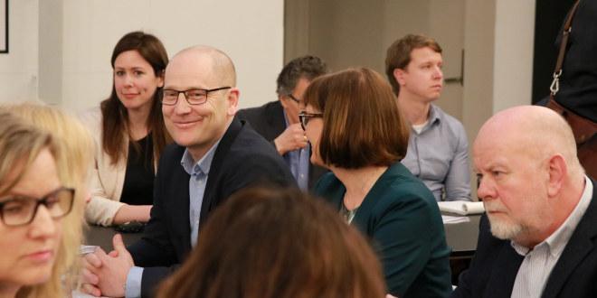 Mann i dress og med briller smiler. Sitter ved et bord sammen med mange andre folk.