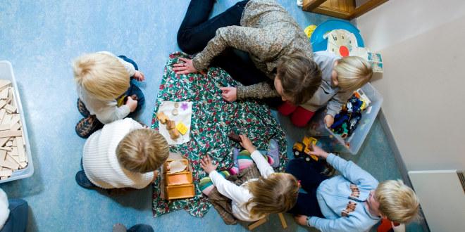 En barnehagelærer sammen med en gruppe barn, sett ovenfra.