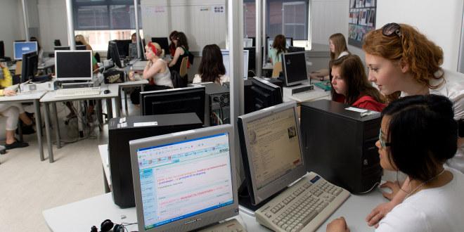 Fra et klasserom med elever foran pc-skjermer. To snakker sammen, ellers sitter alle for seg selv.