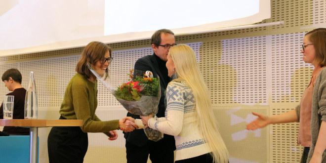 En dame og en mann mottar blomster fra to damer.