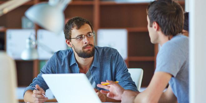 To mannlige kollegaer i samtale ved et bord.