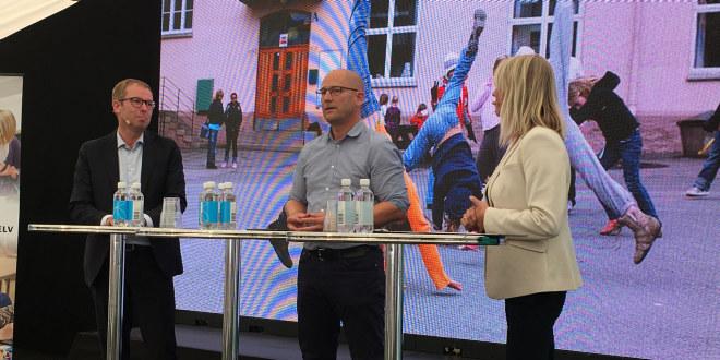 To menn og en dame foran to høye bord med skjerm bak.