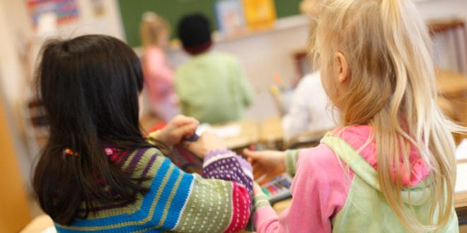 To jenter i et klasserom sitter ved samme pult. Vi ser dem bakfra.