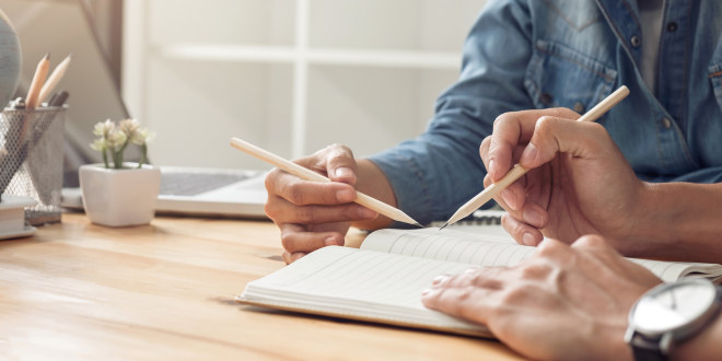 Vi ser hender som holder blyanter og en skrivebok med linjerte ark.