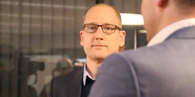 Skallet mann med briller ser inn i kameraet.