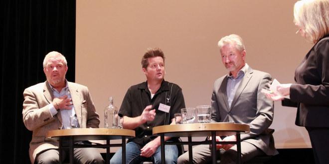 Tre menn sitter ved høye bord. En lys dame i høyre bildekant, stående.
