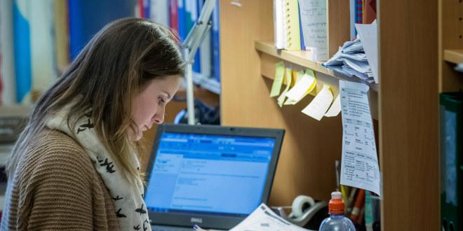 Dame med langt brunt hår sitter på kontorplass med pc ved siden av seg og leser.