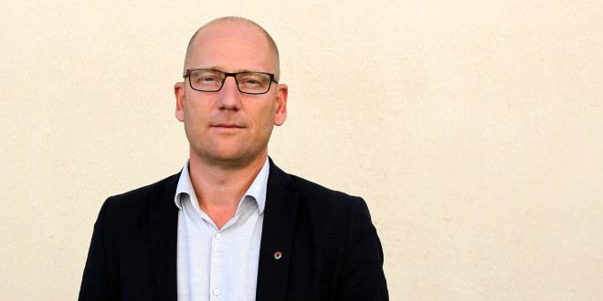 Mann med briller i skjorte og dressjakke ser inn i kamera.