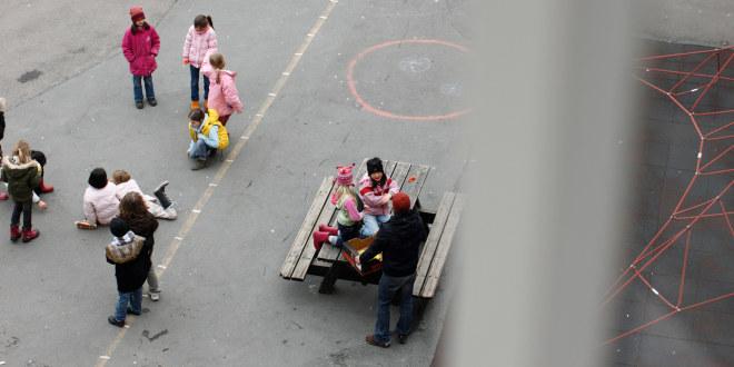 Barn som leker i skolegård, sett ovenfra.
